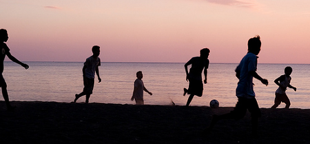Kids playing soccer by sunset