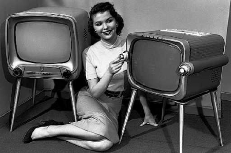 Girl sitting next to old TV's
